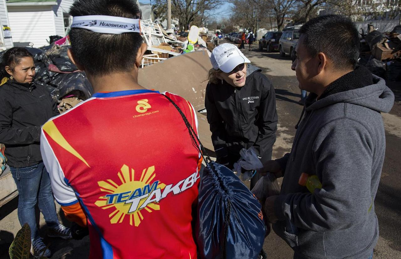Carrying food and other needed goods, Mary Wittenberg, president of the New York Road Runners, second from right, speaks with a person after handing out produce to a family whose house was heavily damaged in the the hard hit Staten Island borough of New York, Sunday, Nov. 4, 2012, in the wake of Superstorm Sandy. With the cancellation of the New York Marathon, hundreds of runners, wearing their marathon shirts and backpacks full of supplies, took the ferry to hard-hit Staten Island and ran to hard-hit neighborhoods to help. (AP Photo/Craig Ruttle)