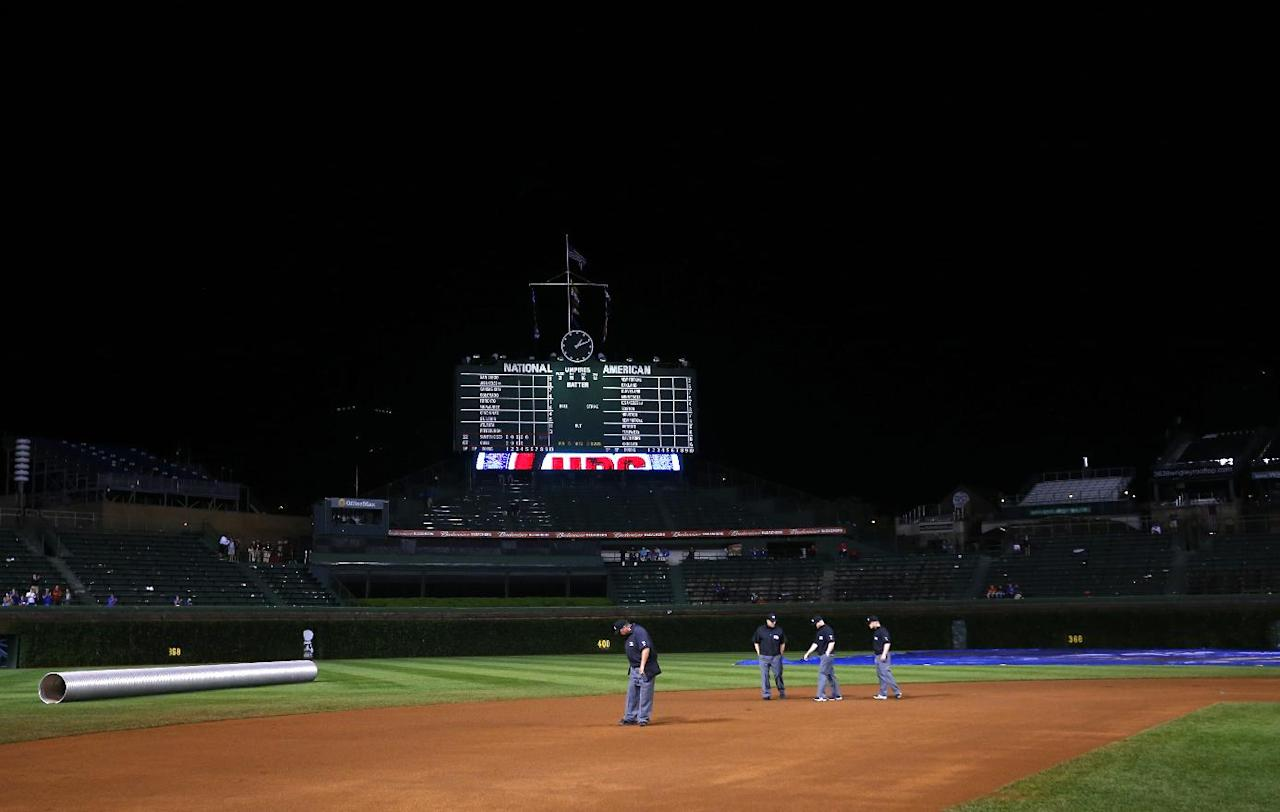 Umpires walk the field for a final time before calling the rain delayed baseball game between the San Francisco Giants and the Chicago Cubs on Tuesday, Aug. 20, 2014, in Chicago. (AP Photo/Jeff Haynes)