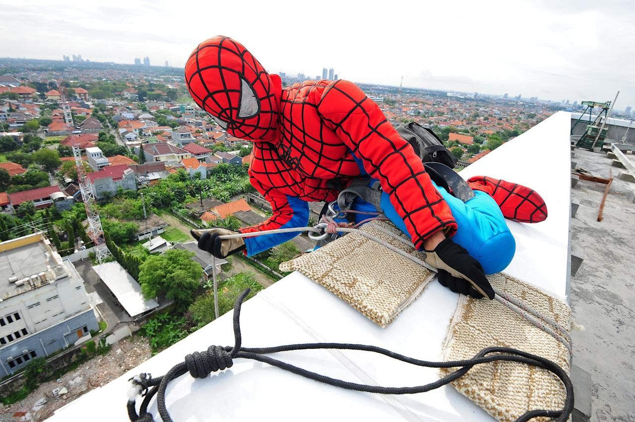 SURABAYA, INDONESIA - JULY 12: Indonesian 'Spider-Man' window cleaner, 37-year-old Teguh prepares his equipment before he cleans the glass windows of the 18-storey Alana Hotel on July 12, 2013 in Surabaya, Indonesia. Teguh is a specialist glass window cleaner working on high-rise buildings wearing a Spider-Man uniform and working at an altitude of over 500 meters above ground level. He earns between Rp. 5 million and 15 million depending on the height of the building and the level of difficulty. (Photo by Robertus Pudyanto/Getty Images)