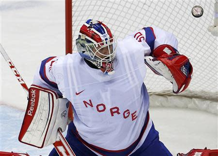 Norway's goalie Haugen makes a save on Austria during the first period of their men's preliminary round ice hockey game at the Sochi 2014 Winter Olympic Games