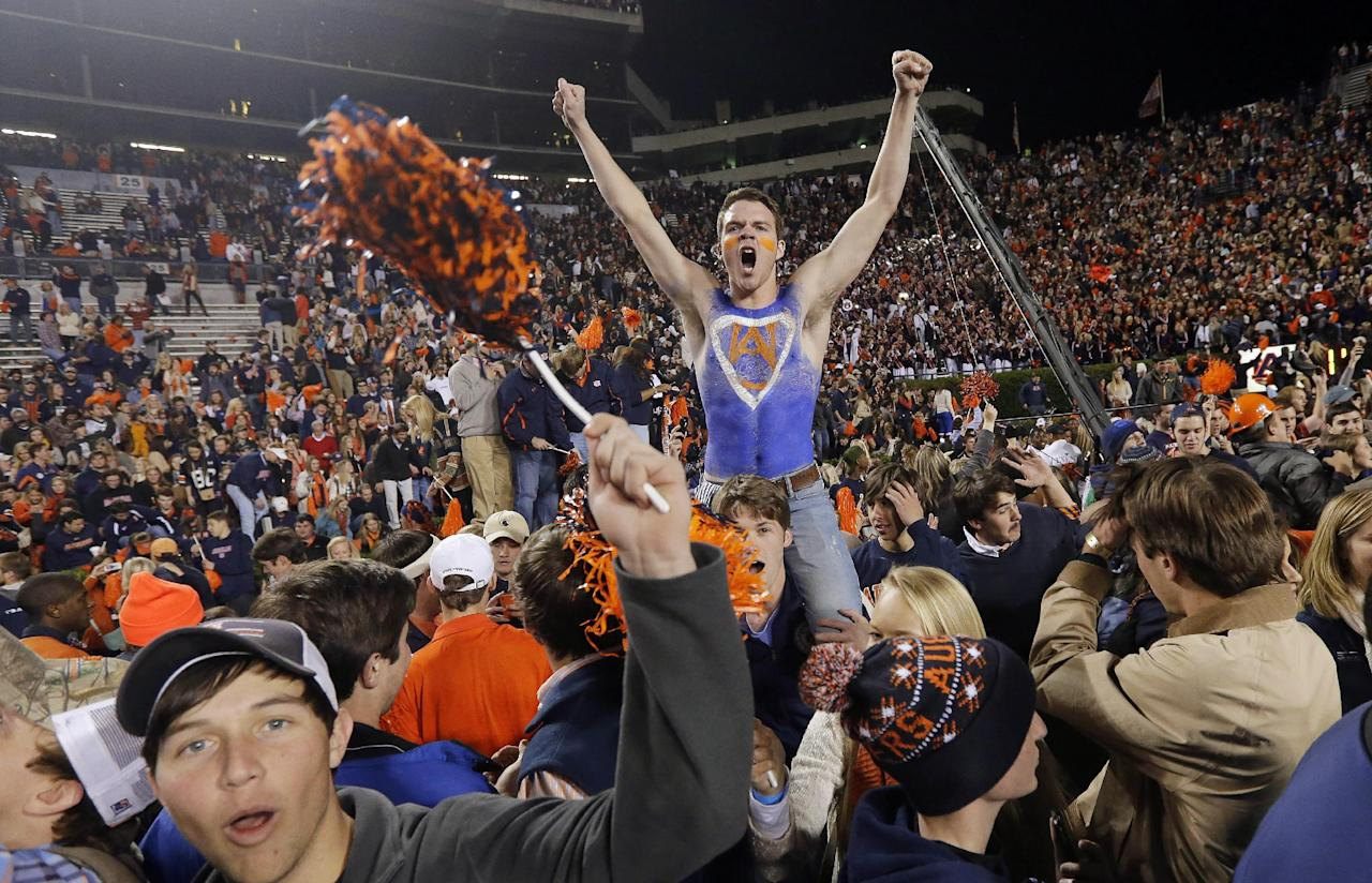 Auburn fans storm the field after their 34-28 after a win over top-ranked Alabama in an NCAA college football game in Auburn, Ala., Saturday, Nov. 30, 2013. (AP Photo/Dave Martin)