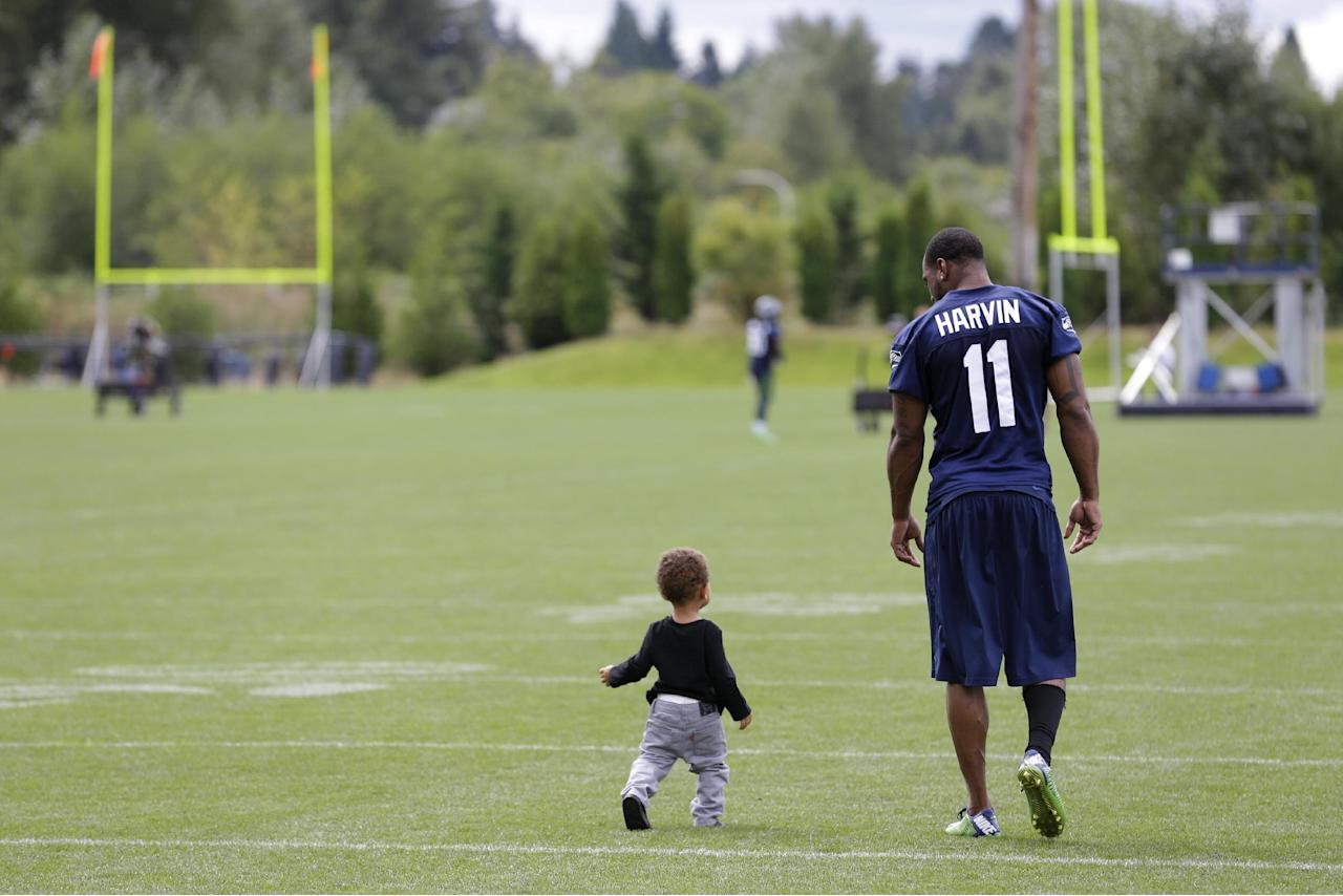 Seattle Seahawks wide receiver Percy Harvin, right, walks with his son Jaden, 1, on the field following the final day of NFL football training camp, Wednesday, Aug. 13, 2014, in Renton, Wash. (AP Photo/Ted S. Warren)