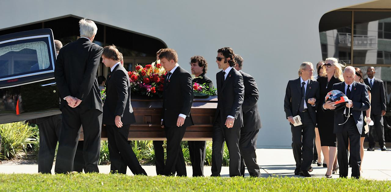 ST PETERSBURG, FL - OCTOBER 22:   Dan Wheldon's widow Susie Wheldon (2nd R), his father Clive (R) and her father Sven Behm (3rdR) look on as Wheldon's casket is loaded into a hearse on October 22, 2011 in St Petersburg, Florida. Wheldon, who was 33 was killed in a 15-car crash at Sunday's season-ending IndyCar race in Las Vegas.  (Photo by Tim Boyles/Getty Images)