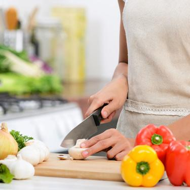 Close-up-of-hands-slicing-vegetables-with-knife_web