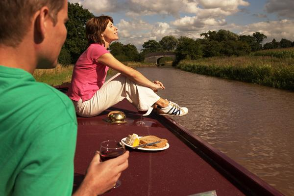 Couple relaxing aboard a narrowboat traveling along the Shropshire Union Canal. VisitBritain/ Adrian Houston