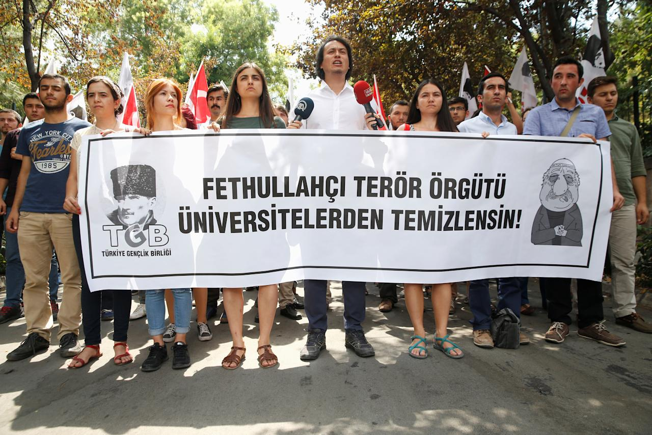 """Members of the ultra-nationalist Turkish Youth Association (TGB) take part in a protest against academics close to U.S.-based cleric Fethullah Gulen in front of Ankara University in Ankara, Turkey, July 21, 2016. The banner reads """"Universities should be cleansed from Fethullah's terrorist organisation"""". REUTERS/Baz Ratner"""