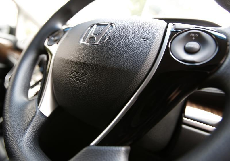 The logo of Honda Motor Co and an airbag logo are seen on a steering wheel in Tokyo