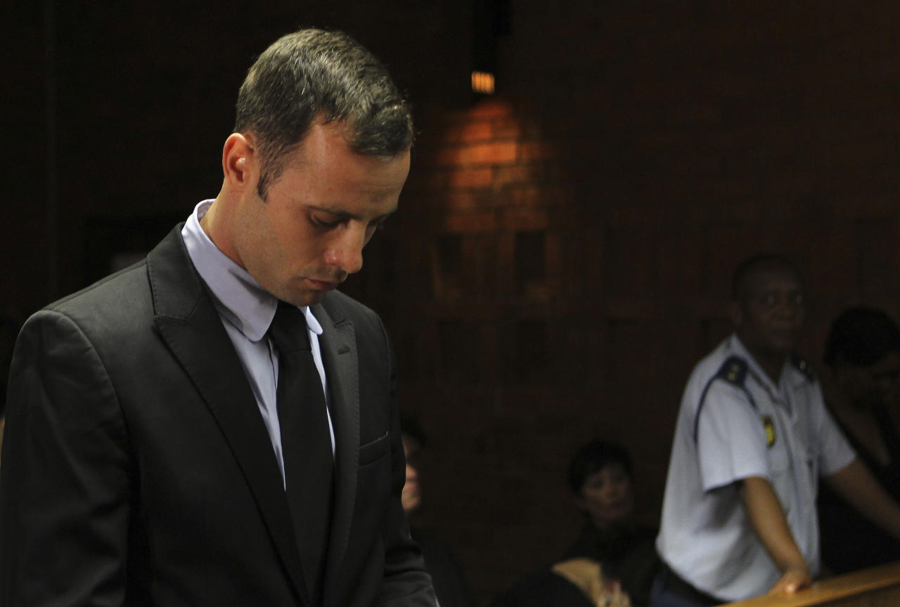 File In this Wednesday, Feb. 20, 2013 file photo Olympic athlete Oscar Pistorius stands inside the court as a police officer looks on during his bail hearing at the magistrate court in Pretoria, South Africa. Pistorius will defend himself against a charge of premeditated murder in the slaying of his girlfriend Reeva Steenkamp, by arguing he believed he was acting lawfully and in self-denense when he fired four shots through a bathroom door in his home with his licensed 9mm handgun, criminal and firearm experts say, even though the Olympic athlete concedes now that he made a deadly error. (AP Photo/Themba Hadebe, File)