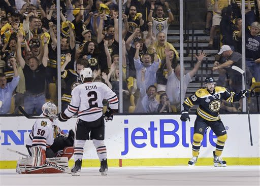 Boston Bruins center Chris Kelly (23) celebrates his goal past Chicago Blackhawks goalie Corey Crawford (50) during the first period in Game 6 of the NHL hockey Stanley Cup Finals, Monday, June 24, 2013, in Boston. Blackhawks defenseman Duncan Keith (2) skates past. (AP Photo/Elise Amendola)