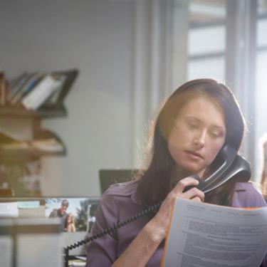 Woman-on-phone-looking-at-paper_web