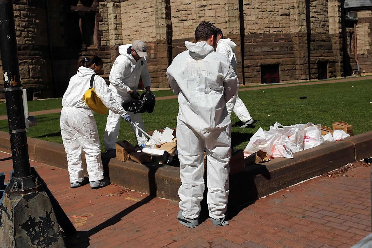 BOSTON, MA - APRIL 17:  Recovery workers, including members of the Federal Bureau of Investigation (FBI), search for clues near the scene of twin bombings at the Boston Marathon on April 17, 2013 in Boston, Massachusetts. The explosions, which occurred near the finish line of the 116-year-old Boston race on April 15, resulted in the deaths of three people with more than 170 others injured. Security has been heightened across the nation as the search continues for the person or people behind the bombings.  (Photo by Spencer Platt/Getty Images)