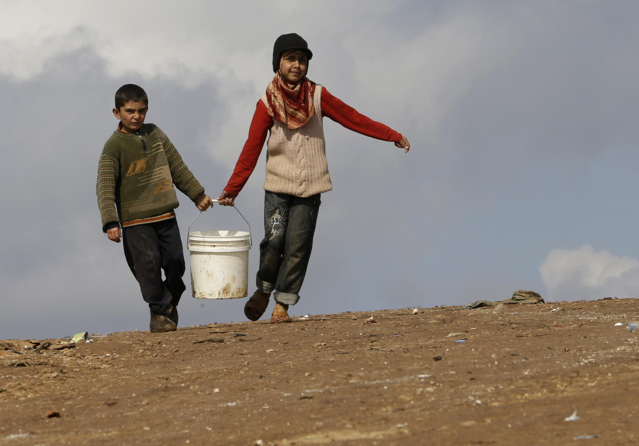 In this Tuesday, Feb. 19, 2013 photo, Syrian refugees carry a bucket of water as they walk at Atmeh refugee camp, in the northern Syrian province of Idlib, Syria. This rebel-controlled camp only yards from the border with Turkey houses some 16,000 people displaced by the civil war. But the U.N. and other major aid agencies best equipped to handle such a large-scale relief agency cannot reach them because they are inside Syria. That leaves the job to smaller organizations who can only provide a fraction of the needs. (AP Photo/Hussein Malla)