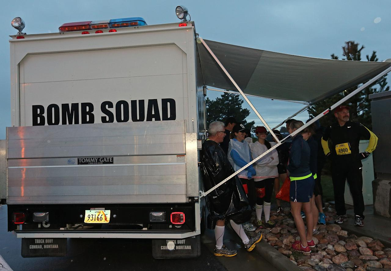 SALT LAKE CITY, UT - APRIL 20: Runners take shelter from the rain by a bomb squad truck before the start of the Salt Lake City Marathon on April 20, 2013 in Salt Lake City, Utah. Due to the bombings at the Boston Marathon on April 15, security was dramatically increased by law enforcement and Utah National Guard at the Salt Lake City Marathon. Organizers are asking spectators to leave backpacks at home. (Photo by George Frey/Getty Images)