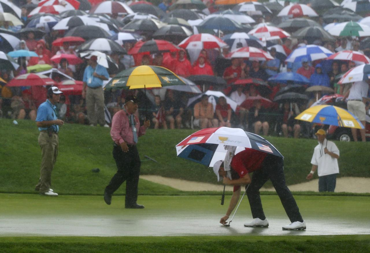 Jordan Spieth of the U.S. picks up his ball off the rain-soaked 14th green as play is suspended during his four ball match with playing partner Steve Stricker against International team players Jason Day of Australia and Graham DeLaet of Canada at the 2013 Presidents Cup golf tournament at Muirfield Village Golf Club in Dublin, Ohio October 5, 2013. REUTERS/Chris Keane (UNITED STATES - Tags: SPORT GOLF ENVIRONMENT)
