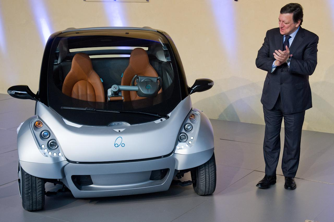 "BRUSSELS, BELGIUM - JANUARY 24:  EU Commission President Jose Manuel Barroso looks at the first prototype of the HIRIKO electric car, during the global launch of Hiriko Driving Mobility at the EU Commssion headquarters on January 24, 2012 in Brussels, Belgium. The electronic eco-friendly vehicle will be manufactured in deprived areas of cities who take up Hiriko's ""social purpose"" model. Malmo in Sweden has already signed up to trial Hiriko with Berlin, Barcelona, Vitoria-Gasteiz (the second largest Basque city), San Francisco, and Hong Kong expected to follow suit.  (Photo by Geert Vanden Wijngaert/Getty Images)"