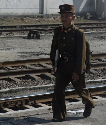 A soldier walks along a train station platform. People affected by the famine in the 90's generally stand out as they are quite short.