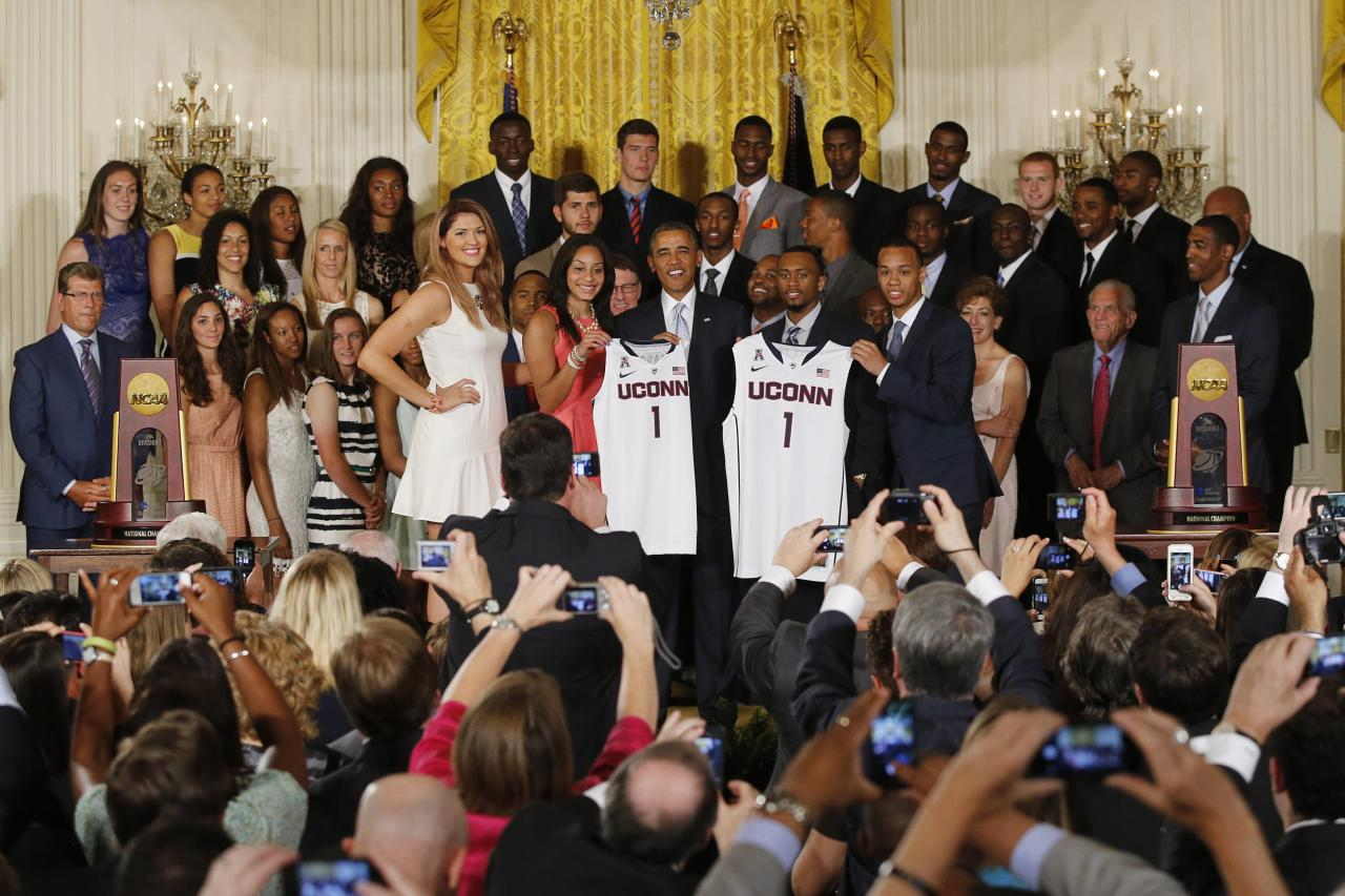 U.S. President Barack Obama poses with UConn women's basketball stars Stefanie Dolson (L) and Bria Hartley (2nd L) and men's team stars Ryan Boatright (2nd R) and Shabazz Napier (R) with jerseys of the NCAA basketball champion University of Connecticut Huskies men's and women's basketball teams in the East Room of the White House in Washington, June 9, 2014. REUTERS/Jim Bourg (UNITED STATES - Tags: POLITICS SPORT BASKETBALL)