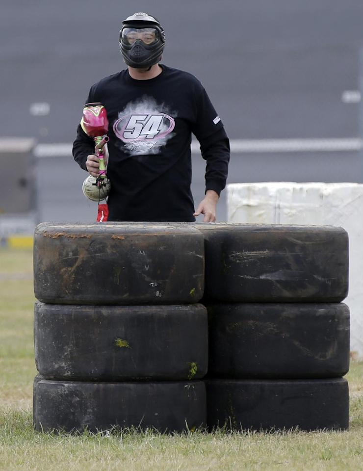 NASCAR driver Kyle Busch looks to shoot during a paintball game against members of the media at Charlotte Motor Speedway in Concord, N.C., Tuesday, Sept. 24, 2013, promoting the upcoming Bank of America 500 NASCAR Sprint Cup auto race on Oct. 12, 2013. (AP Photo/Chuck Burton)