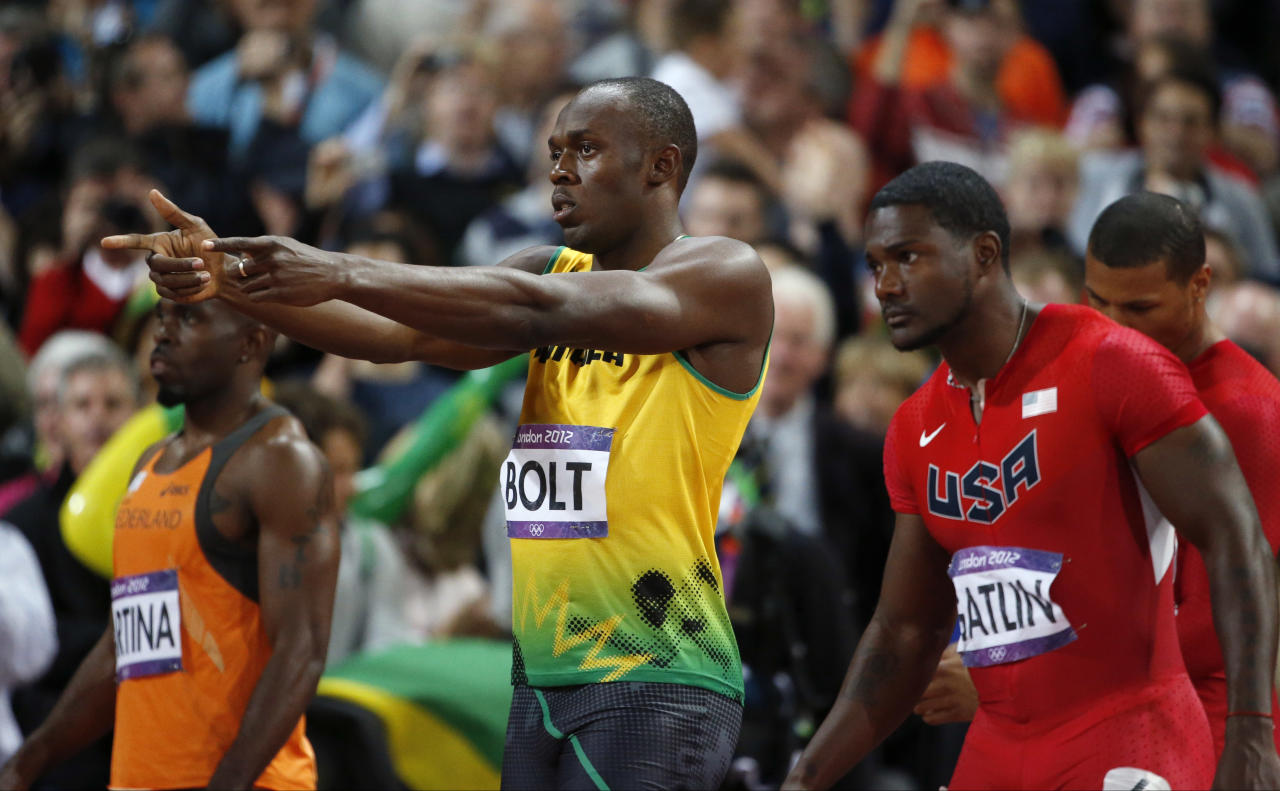 Jamaica's Usain Bolt, center, gestures before competing in the men's 100-meter final alongside United States' Justin Gatlin, right, and Netherlands' Churandy Martina, left, during the athletics in the Olympic Stadium at the 2012 Summer Olympics, London, Sunday, Aug. 5, 2012. (AP Photo/Matt Dunham)