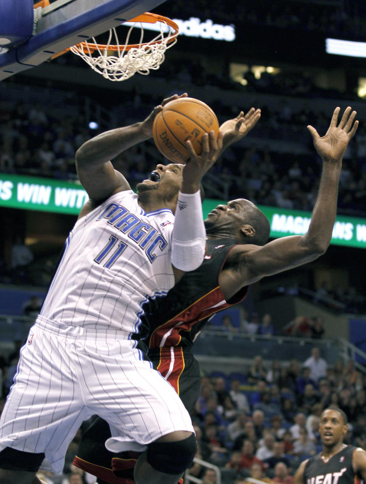 Orlando Magic forward Glen Davis (11) goes up for a basket over Miami Heat center Joel Anthony (50) during the second half of an NBA preseason basketball game, Wednesday, Dec. 21, 2011, in Orlando, Fla. The Magic won 104-100. (AP Photo/Reinhold Matay)
