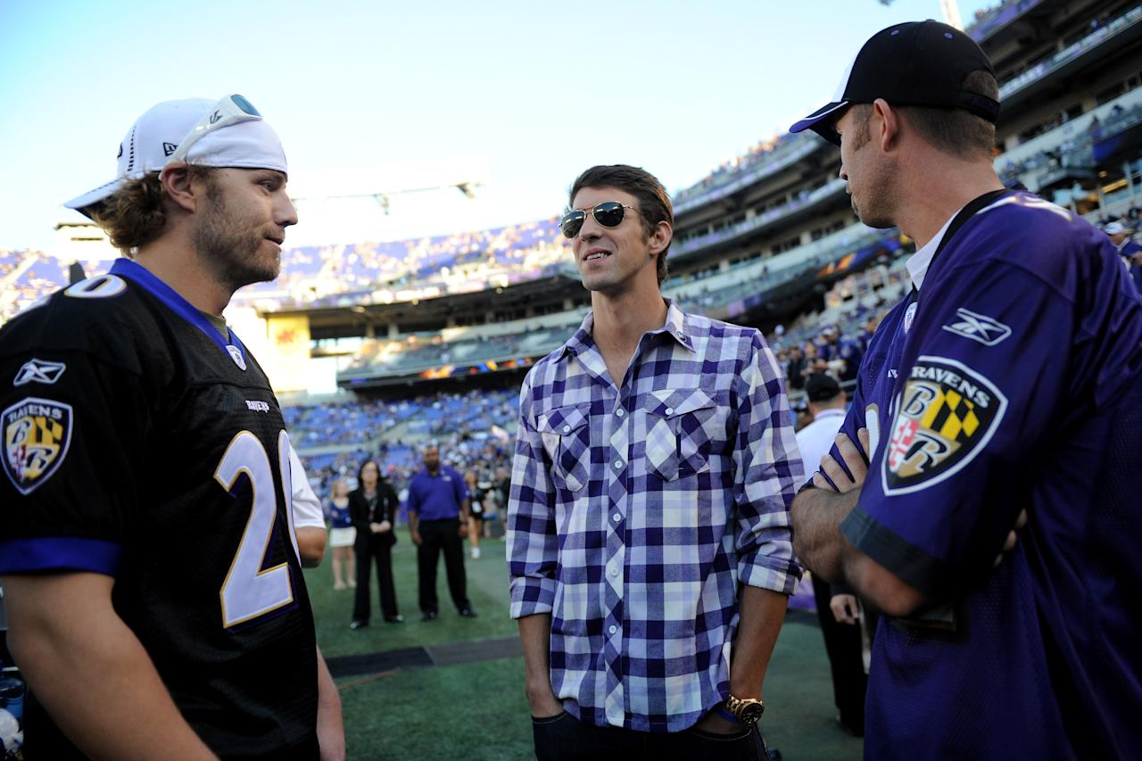 BALTIMORE, MD - SEPTEMBER 10:  (C) Olympic swimmer Michael Phelps talks with (L) Mark Reynolds and J.J. Hardy of the Baltimore Orioles on the field before the Baltimore Ravens take on the Cincinnati Bengals at M&T Bank Stadium on September 10, 2012 in Baltimore, Maryland.  (Photo by Patrick Smith/Getty Images)