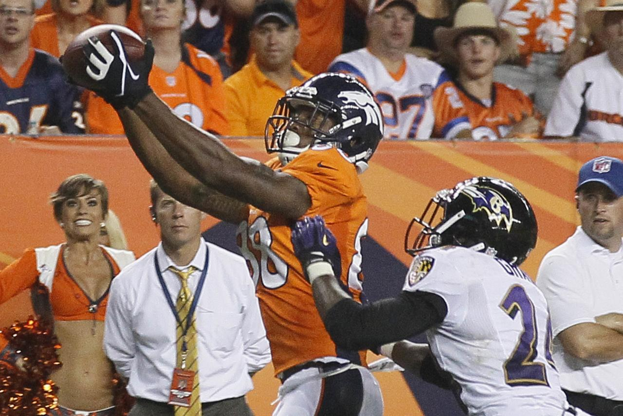 Denver Broncos' Demaryius Thomas (L) catches a touchdown pass in the fourth quarter past Baltimore Ravens' Corey Graham in Denver September 5, 2013. REUTERS/Rick Wilking (UNITED STATES - Tags: SPORT FOOTBALL)