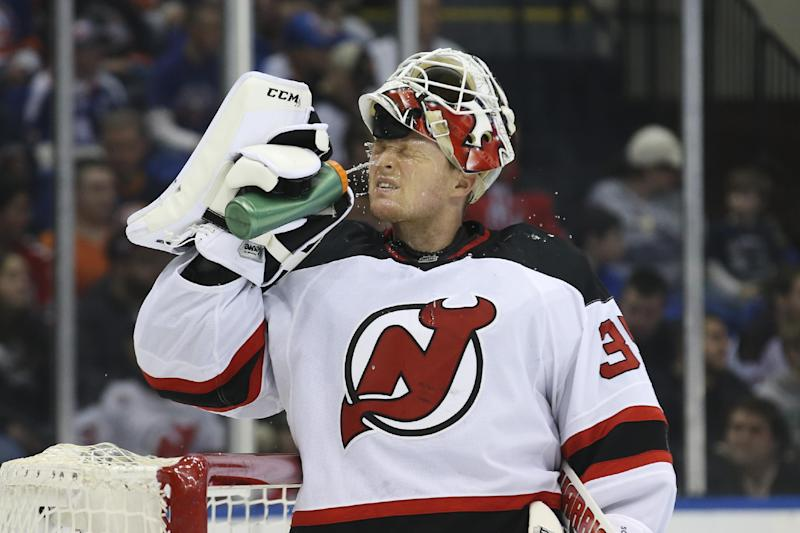 New Jersey Devils goalie Cory Schneider (35) douses himself in the second period of an NHL hockey game against the New York Islanders, Saturday, March 29, 2014, in Uniondale, N.Y