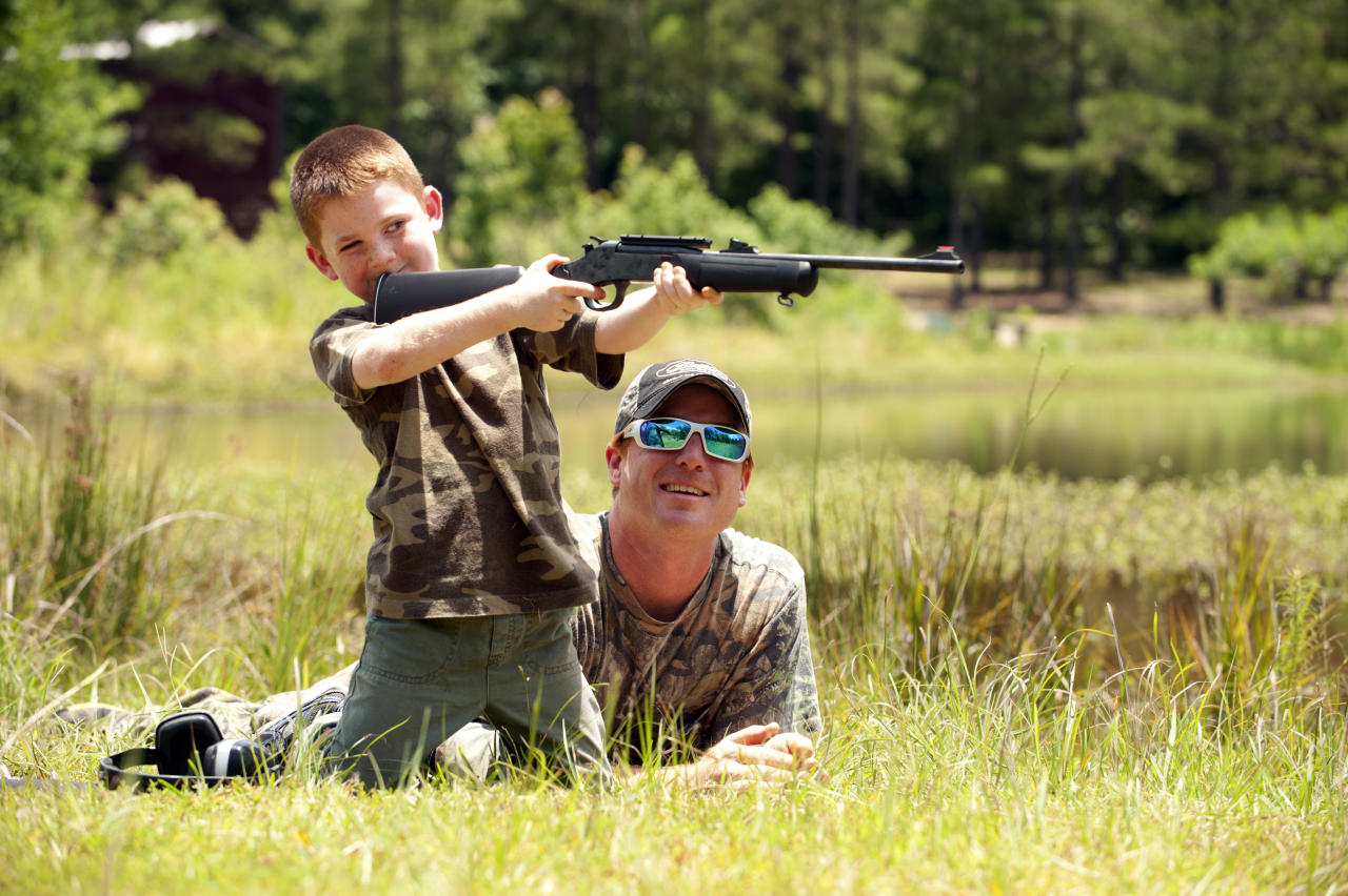 Jeremy Chavez helps his son Ryan, 6, with target practice before a wild hog hunt at Great Southern Outdoors Wildlife Plantation in Union Springs, Alabama, Saturday June 16, 2012. Fast, smart and dangerous, the wild boar was once the most prized hunter's catch in ancient Greece. Now it is becoming a popular target of hunters in the United States. An explosion of wild pig populations has become such a nuisance that hunting seasons are being flung wide open for wild hog across the nation. Picture taken June 16, 2012. REUTERS/Michael Spooneybarger  (UNITED STATES - Tags: ANIMALS SOCIETY)