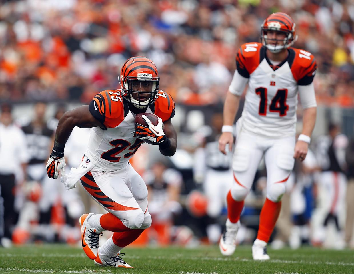 CLEVELAND, OH - SEPTEMBER 29: Half back Giovani Bernard #25 of the Cincinnati Bengals runs the ball as quarterback Andy Dalton #14 looks on against the Cleveland Browns at FirstEnergy Stadium on September 29, 2013 in Cleveland, Ohio. (Photo by Matt Sullivan/Getty Images)