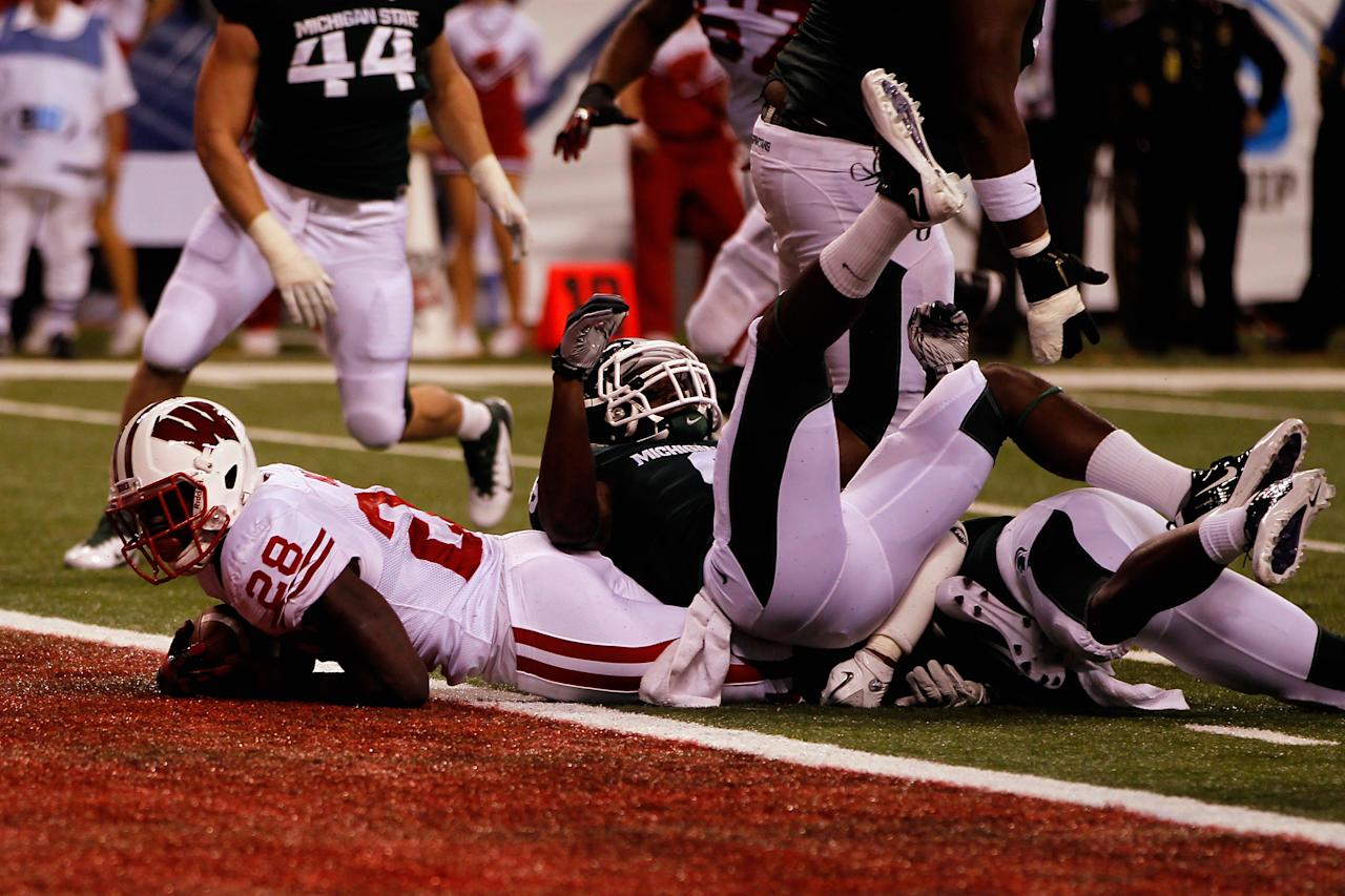INDIANAPOLIS, IN - DECEMBER 03:  Montee Ball #28 of the Wisconsin Badgers scores a 6-yard rushing touchdown in the first quarter against the Michigan State Spartans during the Big 10 Conference Championship Game at Lucas Oil Stadium on December 3, 2011 in Indianapolis, Indiana.  (Photo by Gregory Shamus/Getty Images)