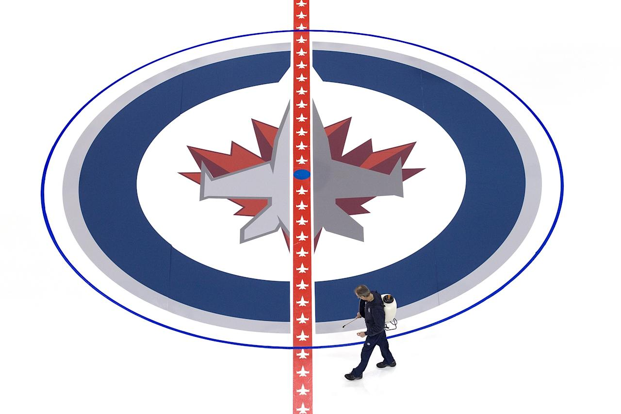 WINNIPEG, CANADA - JANUARY 8: Ice technicians install the Winnipeg Jets logo at centre ice at the MTS Centre on January 8, 2013 in Winnipeg, Manitoba, Canada. (Photo by Marianne Helm/Getty Images)