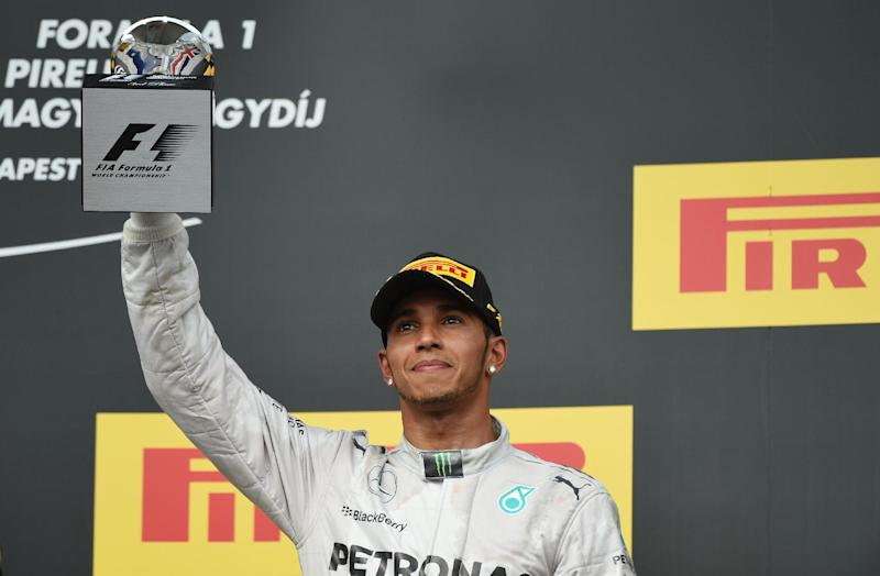 Mercedes' British driver Lewis Hamilton celebrates on the podium after the Hungarian Formula One Grand Prix at the Hungaroring circuit in Budapest on July 27, 2014