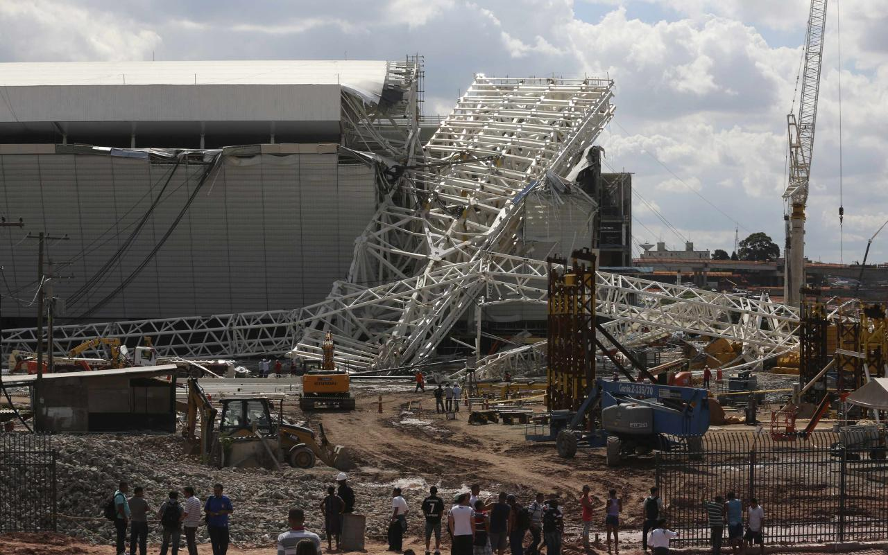 "Workers stand near a crane that collapsed on the site of the Arena Sao Paulo stadium, known as ""Itaquerao"", which will host the opening soccer match of the 2014 World Cup, in Sao Paulo November 27, 2013. A crane collapsed on Wednesday at the construction site of a future World Cup soccer stadium in Sao Paulo, Brazil, killing at least three people and causing damage to the structure, local media said. REUTERS/Nacho Doce (BRAZIL - Tags: SPORT SOCCER WORLD CUP TPX IMAGES OF THE DAY)"