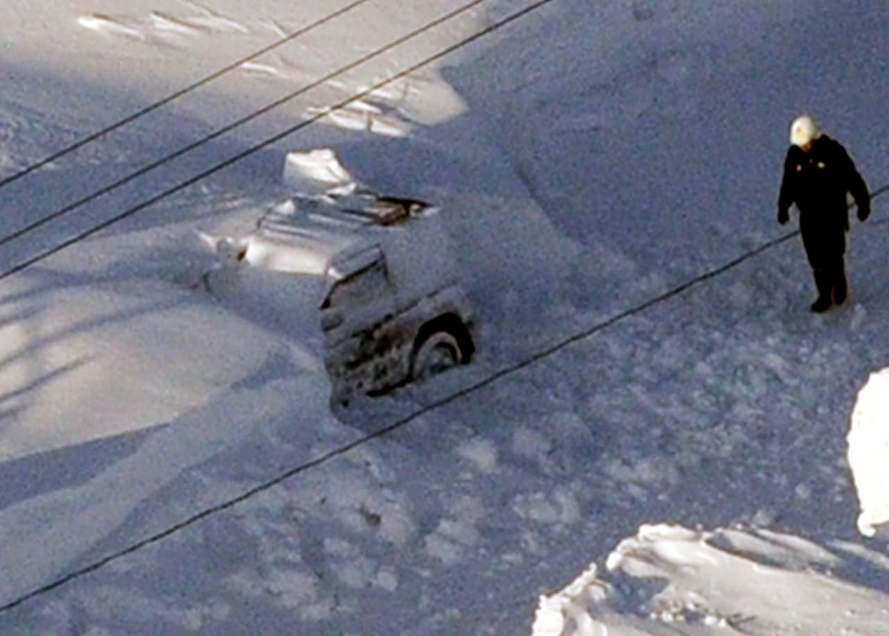 In this photo taken Sunday, March 3, 2013, a policeman inspects the site where a vehicle, center, of Kazuyo Miyashita got buried in the snow along a road in Nakashibetsu, Hokkaido, northern Japan. Kyodo news service says Miyashita and her three children died at a hospital Saturday night of carbon-monoxide poisoning. Heavy snow that fell on the main northern Japanese island of Hokkaido over the weekend has killed eight people, including the family. (AP Photo/Kyodo News) JAPAN OUT, MANDATORY CREDIT, NO LICENSING IN CHINA, HONG KONG, JAPAN, SOUTH KOREA AND FRANCE
