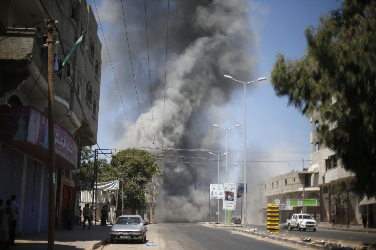 Palestinians gather as smoke rises during what witnesses said was an explosion caused by an Israeli air strike on a house in Gaza City August 23, 2014. Israeli aircraft bombed the Gaza Strip on Saturday and Palestinian militants fired rockets at the Jewish state, the military said, with no end in sight to the deadliest violence between the sides in years. Gaza health officials said five people were killed in an Israeli strike on a house in central Gaza. The Israeli military said it bombed about 20 targets across the Hamas-dominated strip, including rocket launchers and weapon caches. REUTERS/Suhaib Salem (GAZA - Tags: POLITICS CONFLICT)