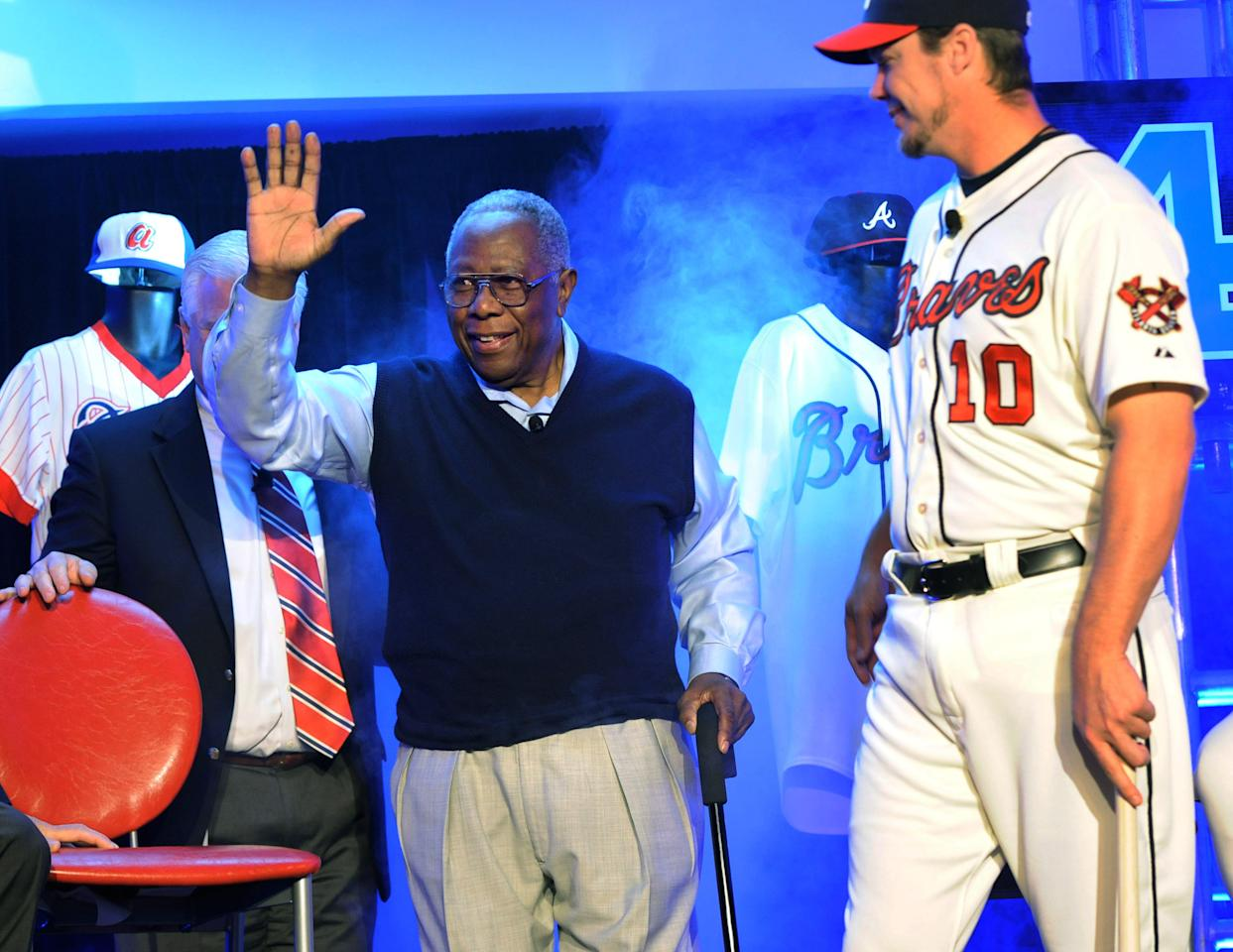 Atlanta Braves' Hank Aaron acknowledges the media while Braves' Chipper Jones looks on when introduced during a news conference to unveil the club's new alternative home uniform, Monday, Feb. 6, 2012, in Atlanta. The uniform pays homage to the team's past, reflecting more of the look of the 1966 team when Aaron played. AP Photo/John Amis)