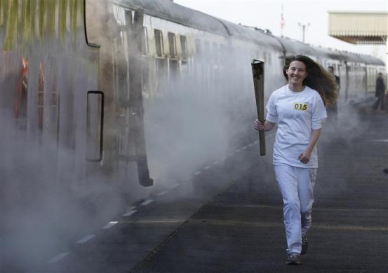 Helana Scott runs with the Olympic torch before boarding a train during the London 2012 Olympic Games Torch Relay rehearsal at Great Central Railway in Leicester, central England April 20, 2012.
