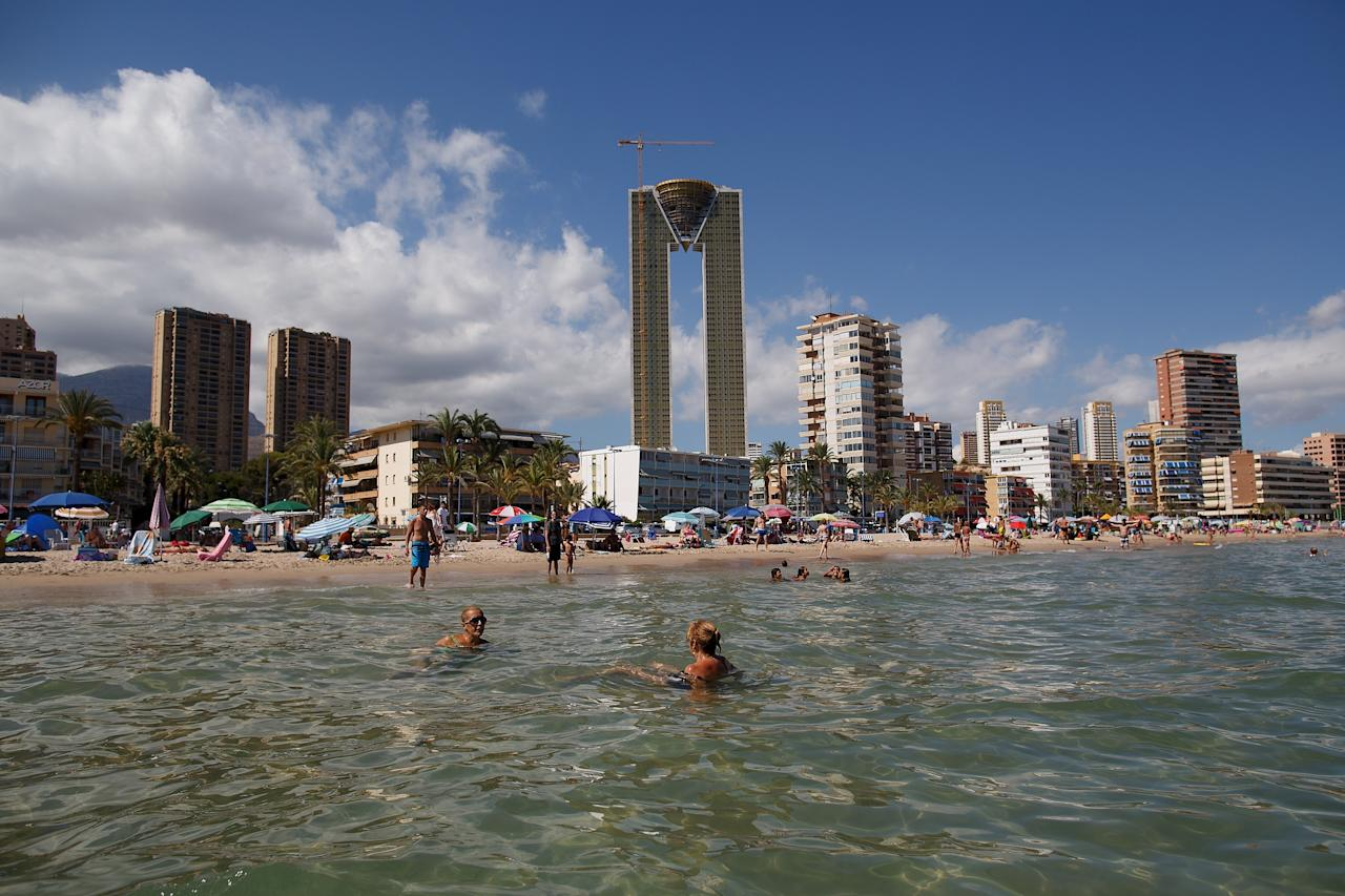 """BENIDORM, SPAIN - AUGUST 09: People swim in the water at Poniente Beach as the unfinished InTempo building stands over them in the distance on August 9, 2013 in Benidorm, Spain. The construction of the In Tempo building began during the economic boom and was meant open in 2009 as the tallest residential building within the E.U. at almost 200 metres high. However after a catalogue of building problems the 47-story twin tower building remains unfinished and has been transferred to the SAREB or """"Bad Bank"""". (Photo by Pablo Blazquez Dominguez/Getty Images)"""