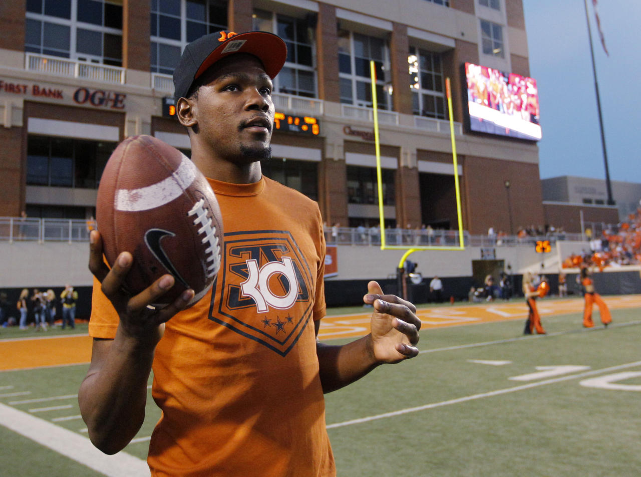 Oklahoma City Thunder's Kevin Durant, who attended the University of Texas, tosses a football around on the sidelines during the first quarter of an NCAA college football game between Oklahoma State and Texas in Stillwater, Okla., Saturday, Sept. 29, 2012. (AP Photo/Sue Ogrocki)