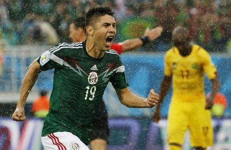 Mexico's Peralta celebrates his goal against Cameroon during their 2014 World Cup Group A soccer match at the Dunas arena in Natal