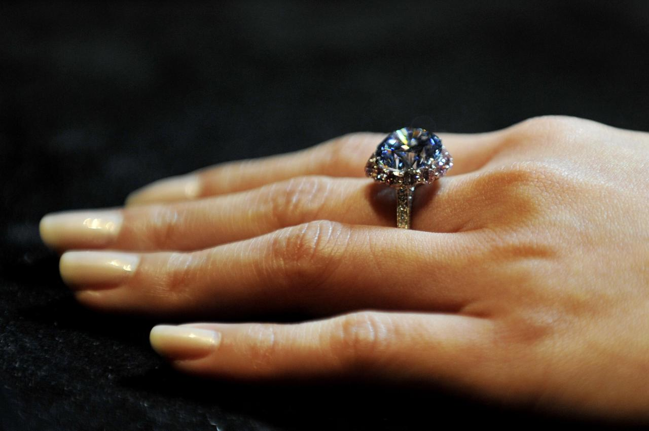 A Sotheby's employee shows the world's largest round fancy vivid blue diamond, a 7.59 Carat stone, estimated in excess of 12 million at Sotheby's, central London, during a preview of the auction house's forthcoming London Rocks sale in October, when two diamonds, the white diamond at 118.28 carats, the largest D colour Flawless diamond, estimated between 18-22 million and round fancy vivid blue diamond are expected to fetch over 30 million between them at the sale.
