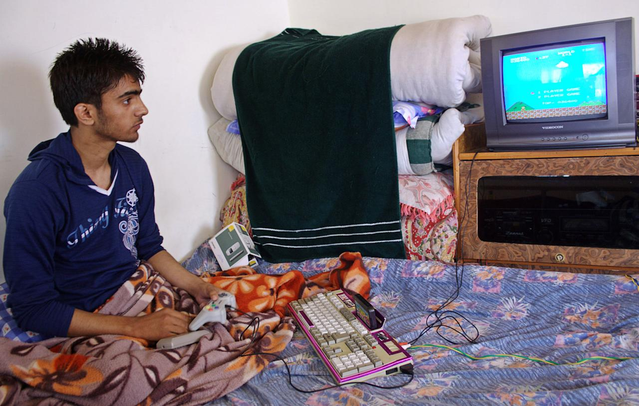 SRINAGAR, KASHMIR - AUGUST 26:  Muneer Ahmad, 16, plays a video game as he sits in his bed inside his house on August 26, 2009 in Srinagar in Indian Administered Kashmir. Muneer has remained bed-ridden for the last four years after a stray bullet hit his spinal chord while he was playing cricket outside his home.  (Photo by Yawar Nazir/Getty Images)
