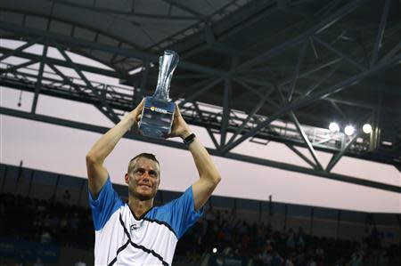 Hewitt of Australia holds Brisbane International men's singles trophy after defeating Federer of Switzerland in Brisbane