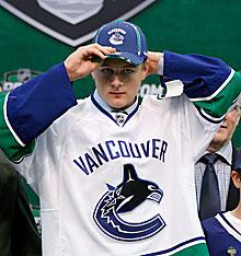 Nicklas Jensen puts on a hat after he was drafted by the Vancouver Canucks in the first round of the NHL entry draft