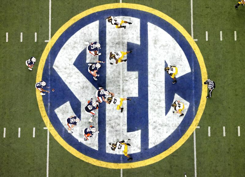 Auburn quarterback Nick Marshall (14), left, takes the snap from Auburn center Reese Dismukes (50) as the Auburn offense operates against Missouri on the SEC logo during the first half of Auburn's 59-42 win over Missouri in the SEC Championship at the Georgia Dome Saturday afternoon in Atlanta, Ga., Dec. 7, 2013