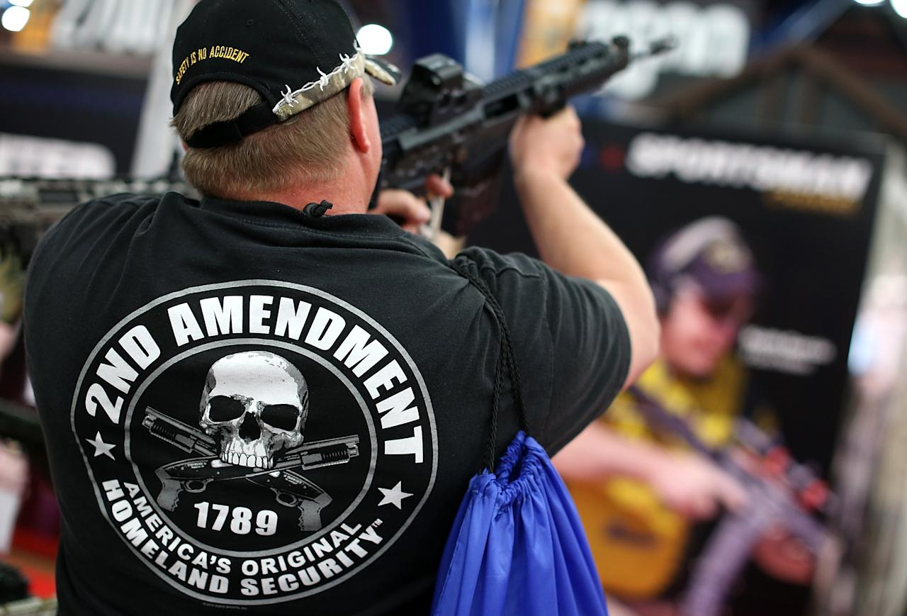 HOUSTON, TX - MAY 05:  An attendee wears a 2nd amendment shirt while inspecting an assault rifle during the 2013 NRA Annual Meeting and Exhibits at the George R. Brown Convention Center on May 5, 2013 in Houston, Texas.  More than 70,000 people attended the NRA's 3-day annual meeting that featured nearly 550 exhibitors, a gun trade show and a political rally.  (Photo by Justin Sullivan/Getty Images)