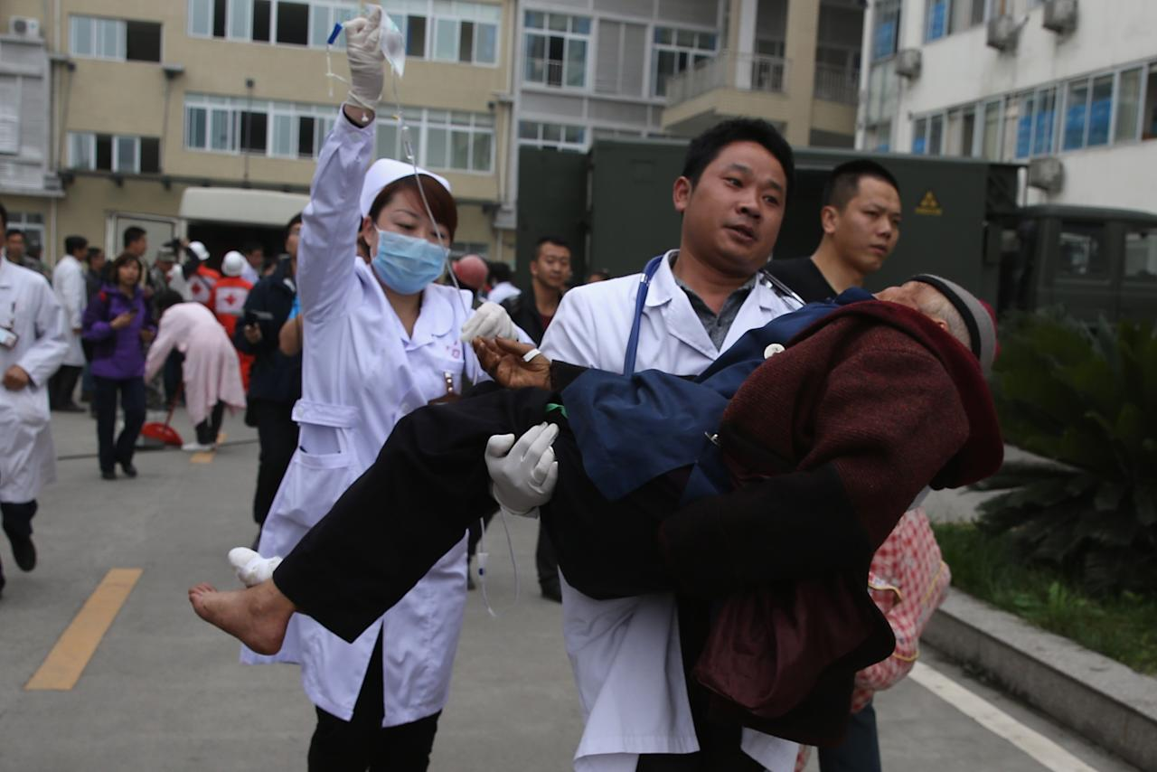 CHENGDU, CHINA - APRIL 22:  Medical officers carries a patient to an ambulance at the hospital on April 22, 2013 in Lushan of Ya An, China.  A magnitude 7 earthquake hit China's Sichuan province on April 20 claiming over 180 lives and injuring thousands.  (Photo by Feng Li/Getty Images)