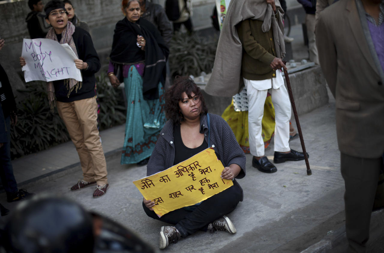 """An Indian protester holds a placard as she sits on a sidewalk during a protest in New Delhi, India, Wednesday, Dec. 19, 2012. The hours-long gang-rape and near fatal beating of a 23-year-old student on a bus in New Delhi triggered outrage and anger across the country Wednesday as Indians demanded action from authorities who have long ignored persistent violence and harassment against women. The placard reads """"I have the right to live in the country."""" (AP Photo/Altaf Qadri)"""