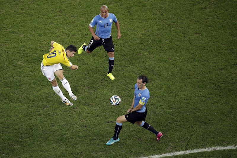 Colombia's James Rodriguez, left, scores the opening goal past Uruguay's Diego Godin, front, as Uruguay's Egidio Arevalo Rios gives chase during the World Cup round of 16 soccer match between Colombia and Uruguay at the Maracana Stadium in Rio de Janeiro, Brazil, Saturday, June 28, 2014