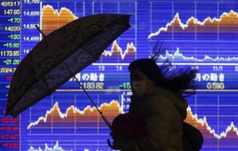 A pedestrian holding an umbrella walks past an electronic board showing the graph of the recent fluctuations of Japan's Nikkei average outside a brokerage in Tokyo